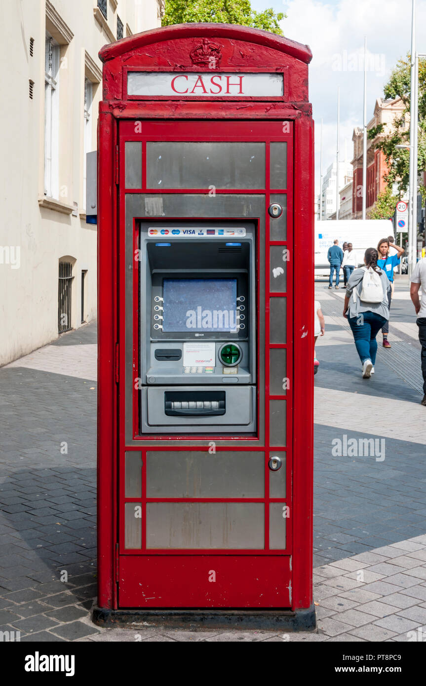 A telephone kiosk re-purposed as a cash machine. - Stock Image
