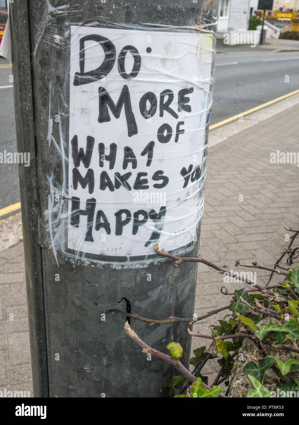 'Do More of What Makes You Happy' sign on a street light mast in Newquay, Cornwall. - Stock Image