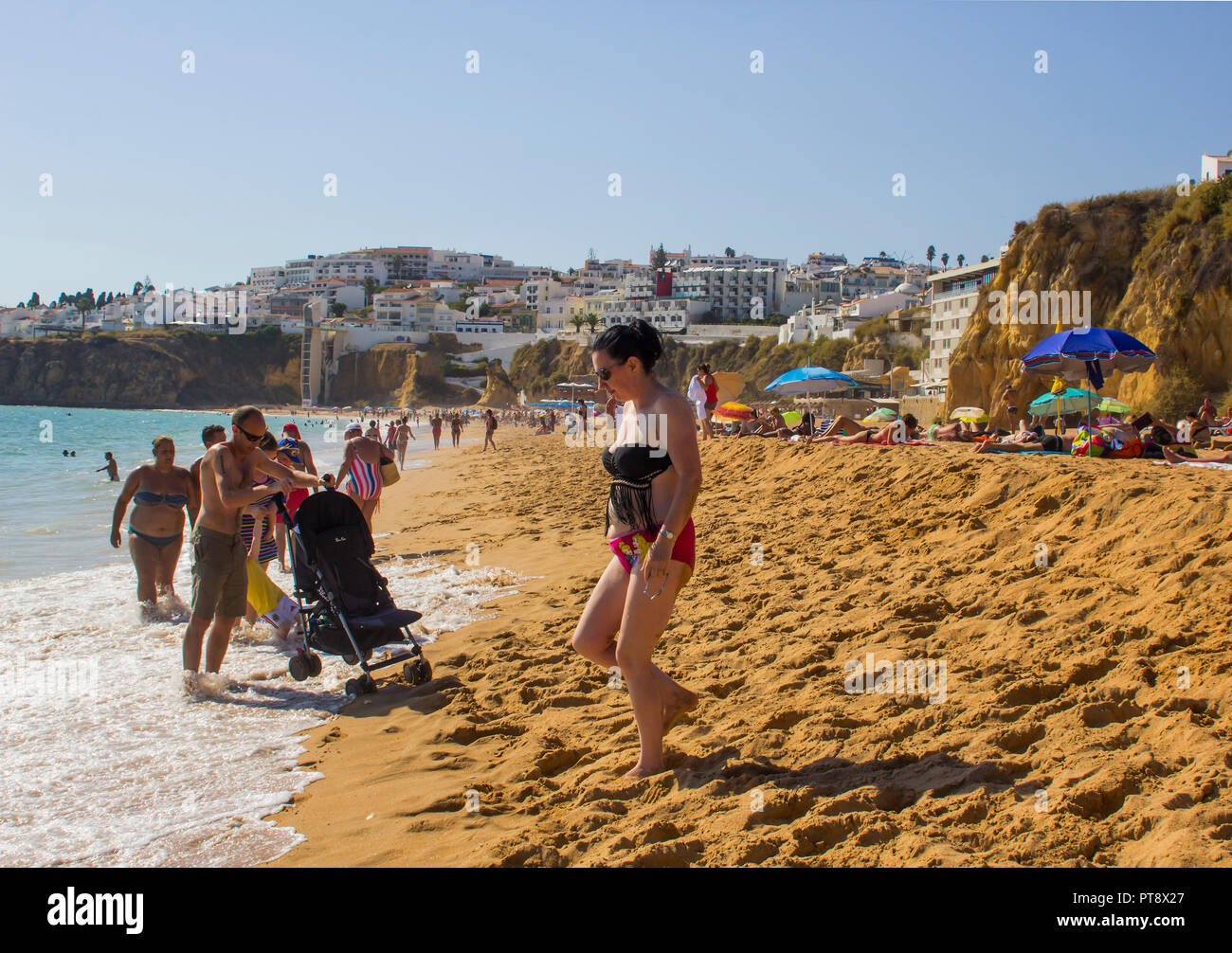 28 September 2018 A view along the crowded Praia Dos Pescadores toward the Old Town Albuferia on the Algarve Portugal with sun beds and sand - Stock Image