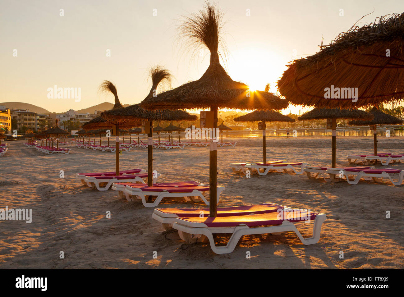 Empty chairs and straw umbrellas on the Alcudia beach in Majorca at sunrise Stock Photo