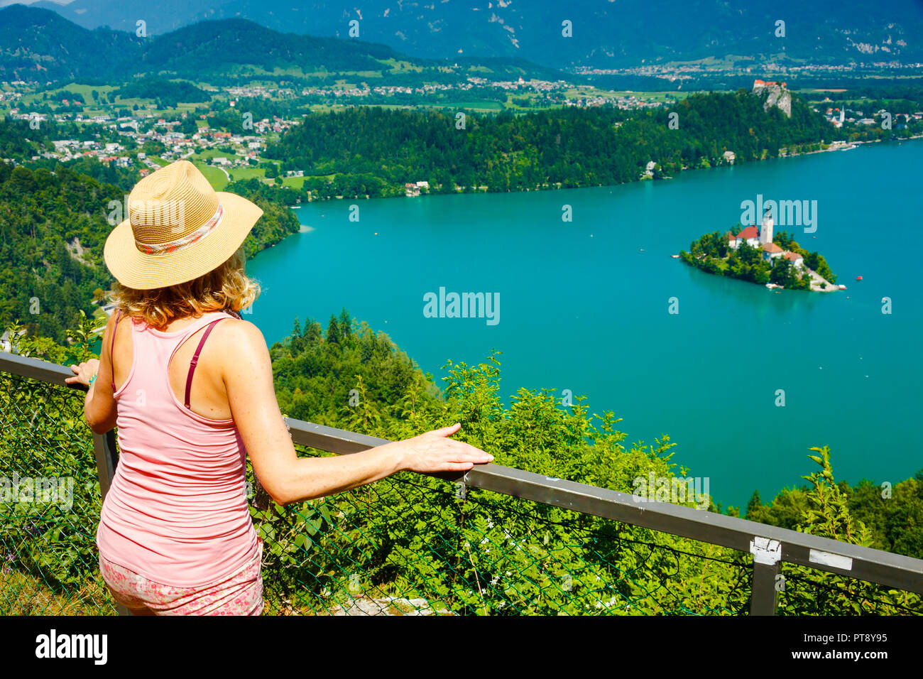 Woman looking a lake landscape from a viewpoint. - Stock Image