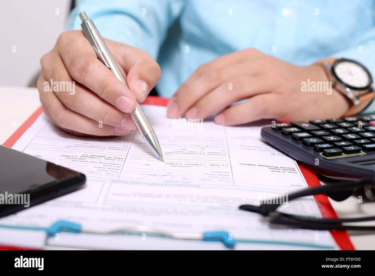 Man is filling form with pen. Picture of form on the clipboard. Portrait of glasses, calculator and phone on the form. Stock Photo