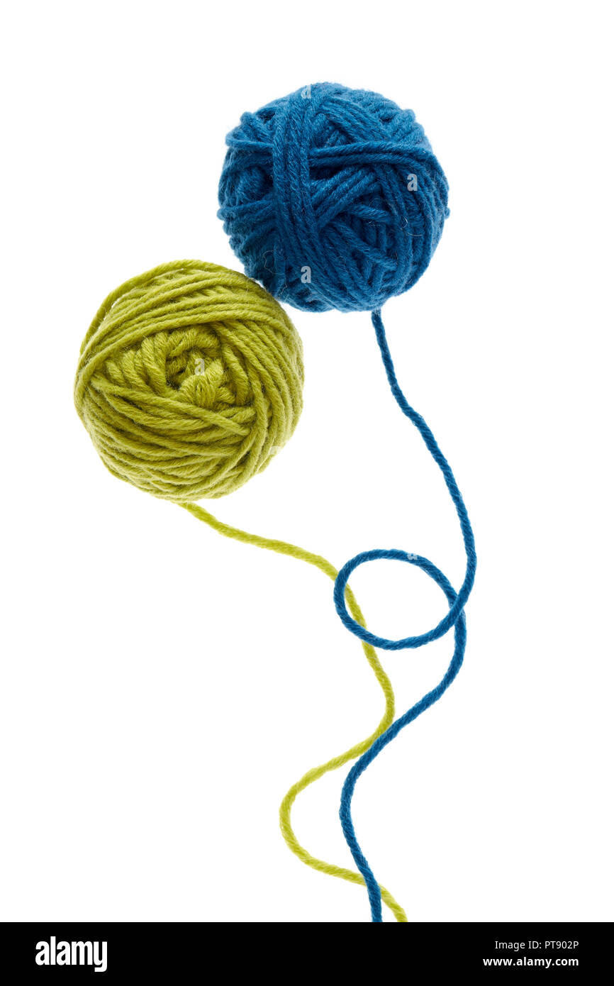 Blue and green woolen balls over white background. Two balls of wool partially unrolled. - Stock Image