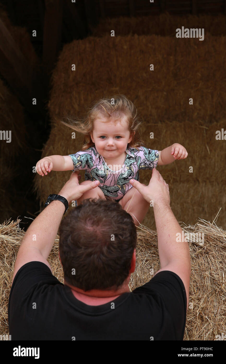 Toddler jumping into her fathers arms. - Stock Image