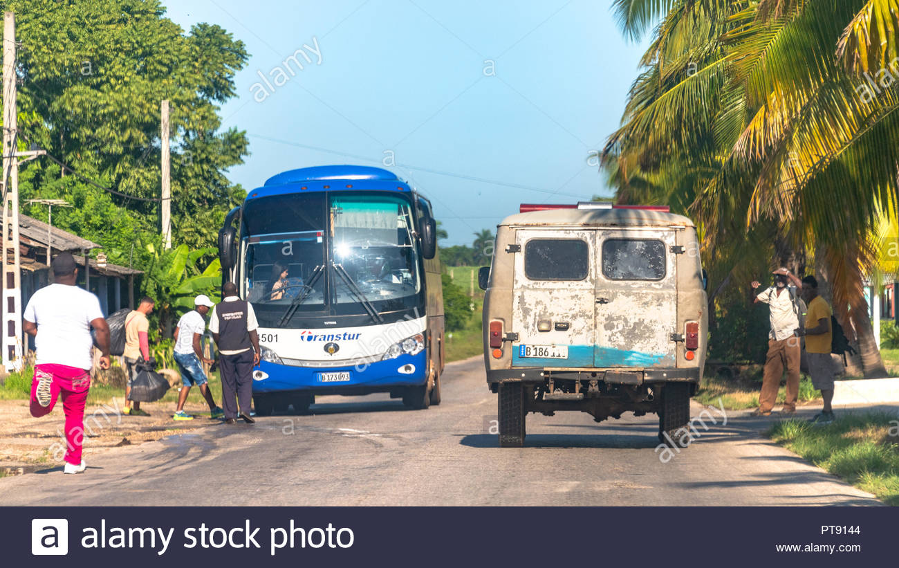 Real life in Cuba: an old ambulance drives on a country road while a man runs to catch a tourist bus. Contrasts in the Caribbean lifestyle - Stock Image