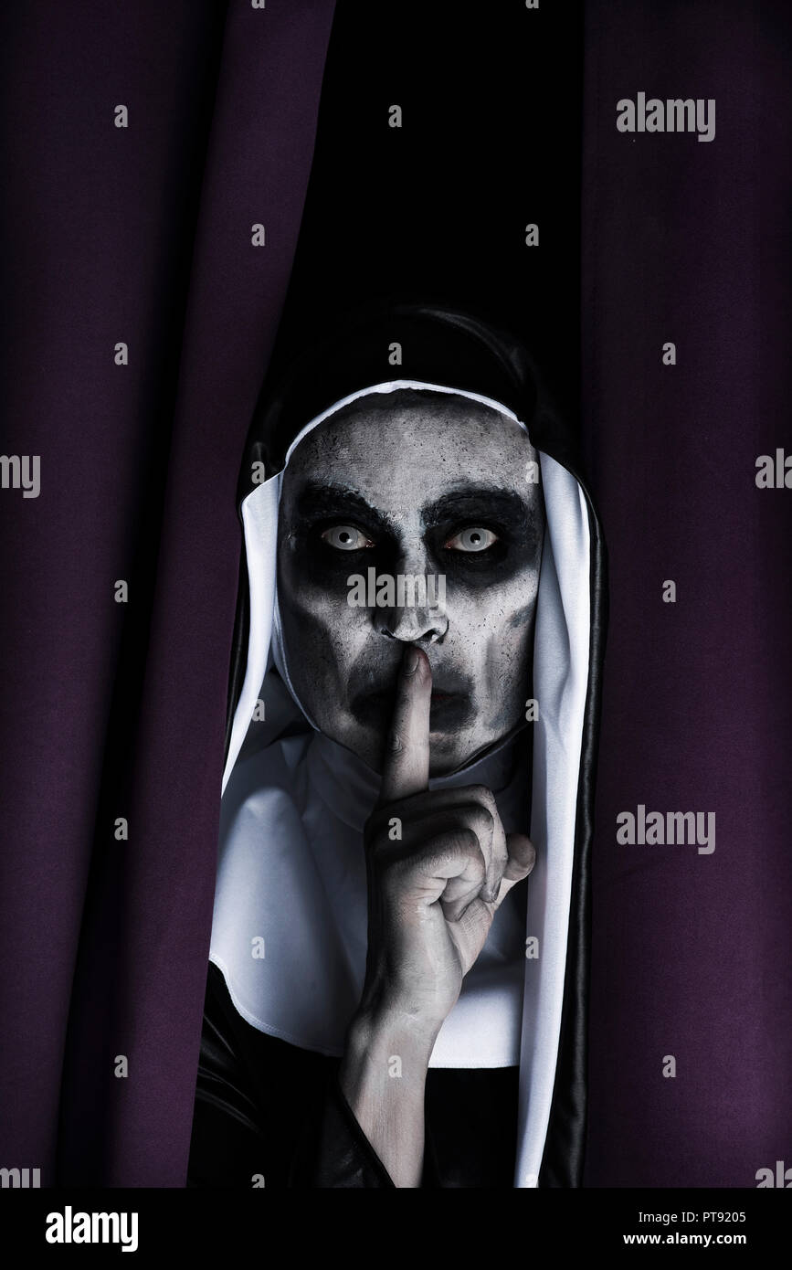 closeup of a frightening evil nun, wearing a typical black and white habit, peeping out from a purple curtain, asking for silence - Stock Image