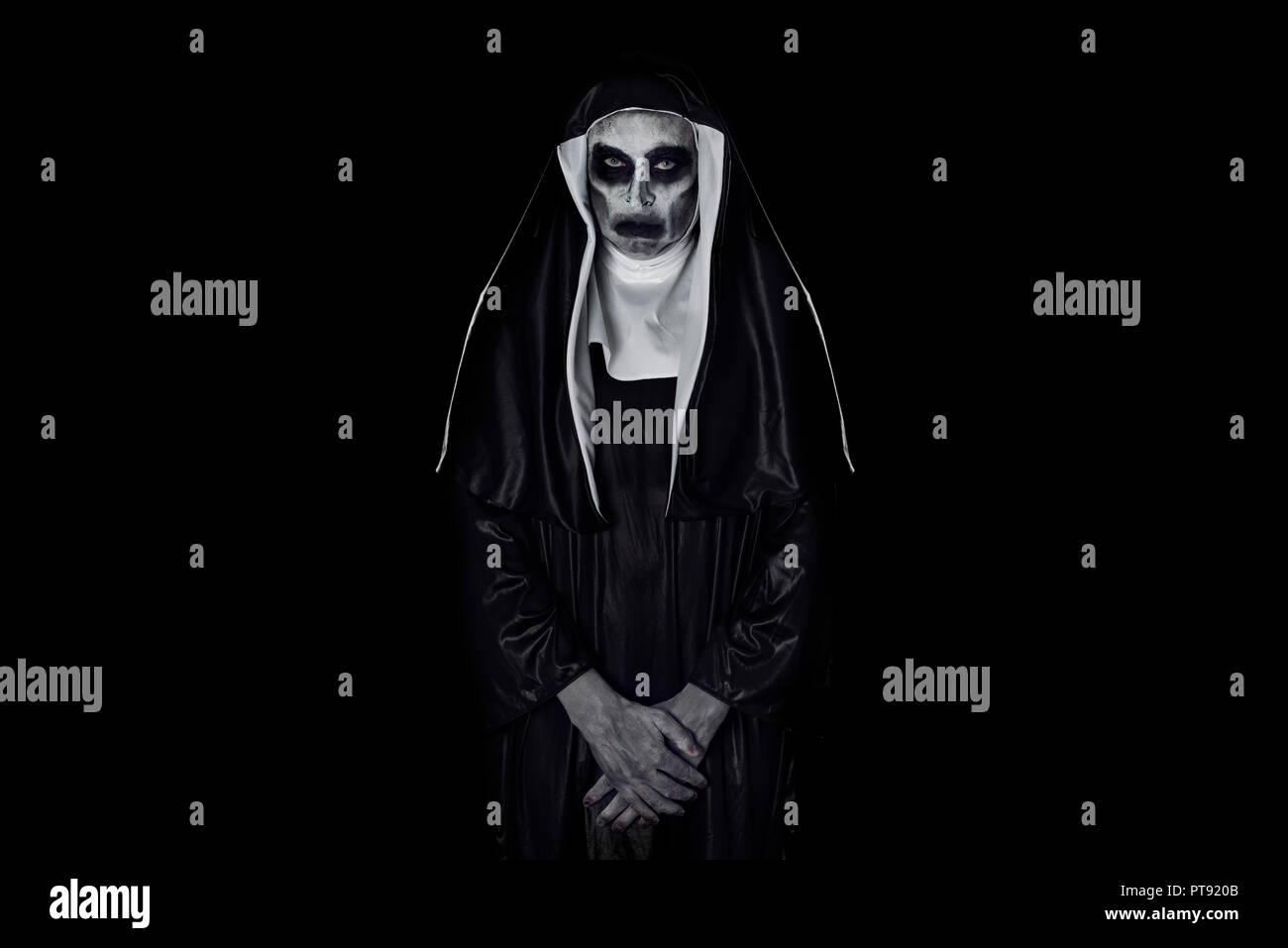portrait of a frightening evil nun, wearing a typical black and white habit, against a black background, with some blank space around her - Stock Image