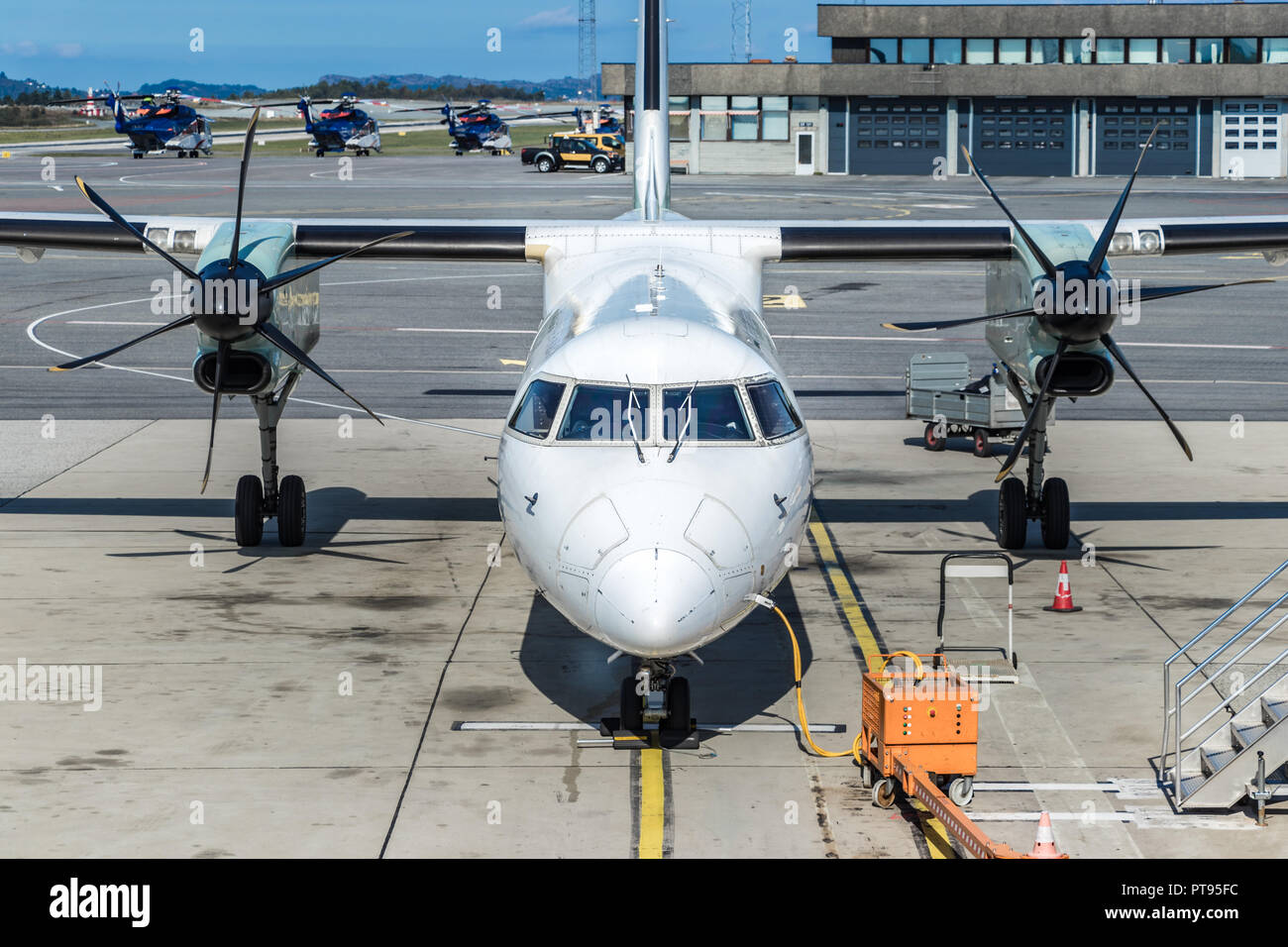 An passenger airplane twin turboprop parked next to a jetway at Begen International Airport, Norway. - Stock Image
