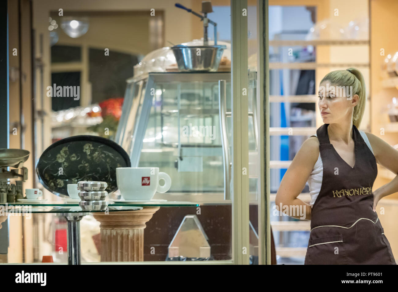 Pylos, Greece - October 2th, 2018: A  woman working in a bakery - pastry store is standing at the entrance outdoors looking away at the commercial cen - Stock Image