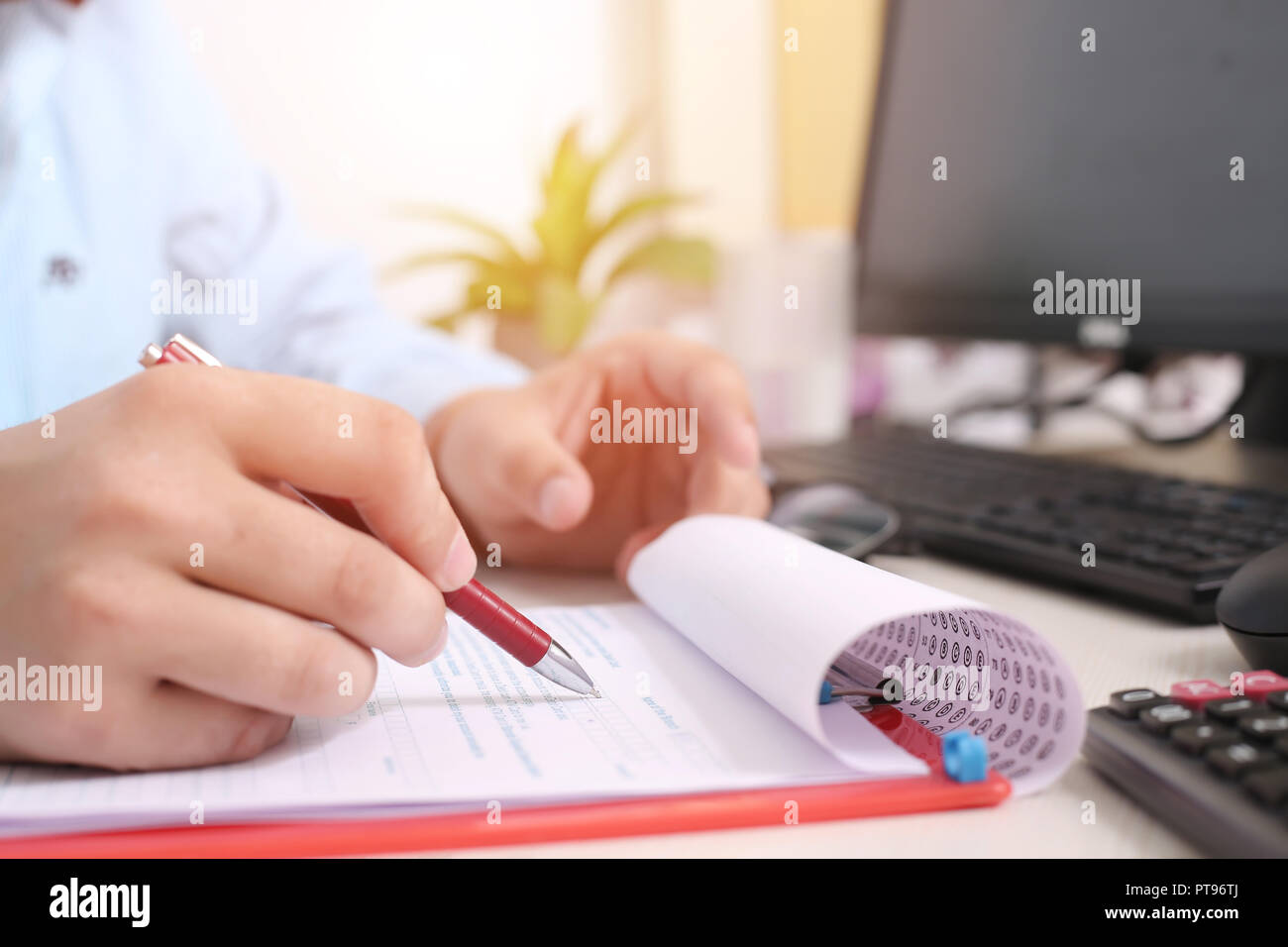 Man is filling form with pen. Picture of computer and keyboard with form on the clipboard. Stock Photo