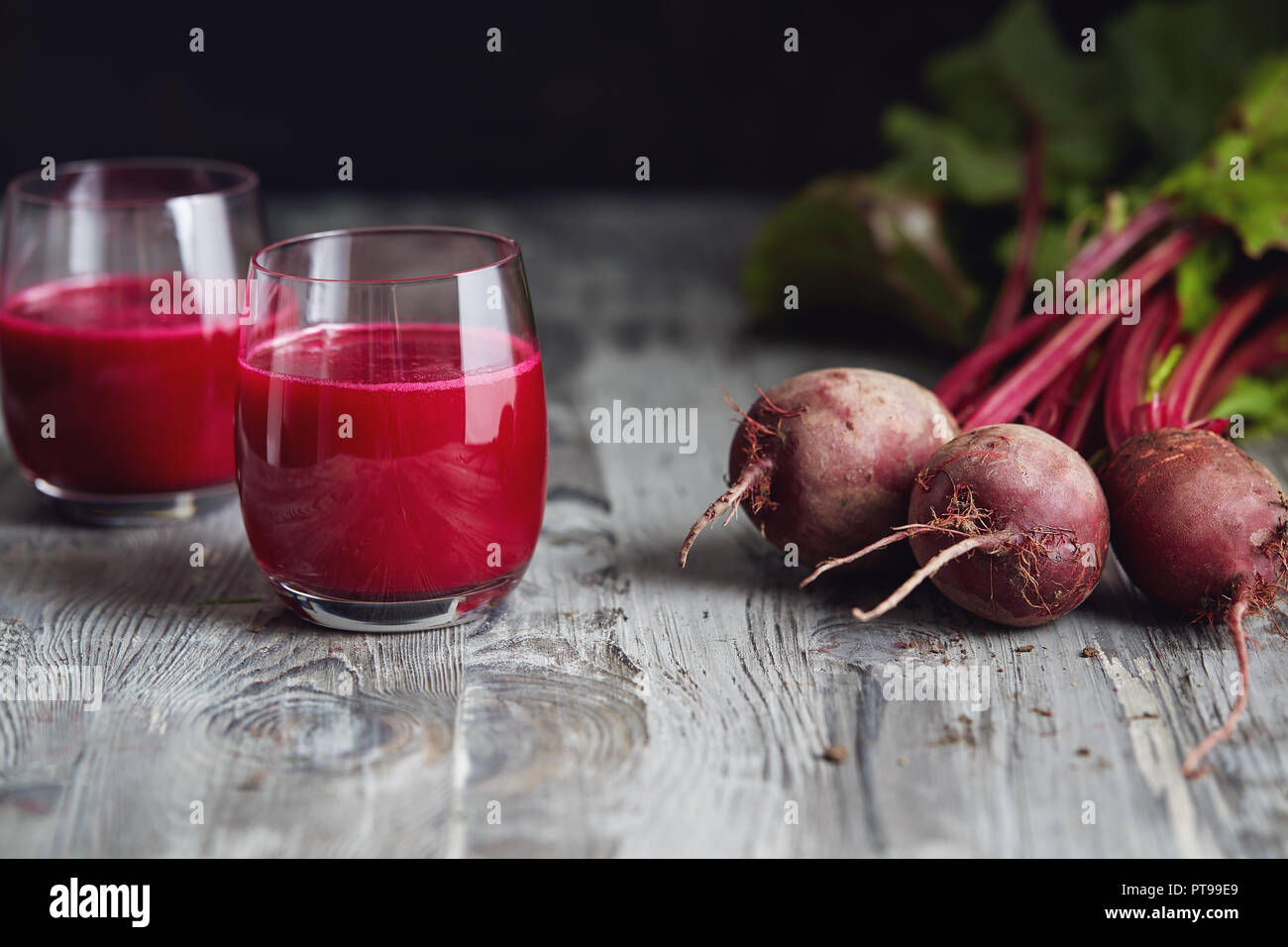 Detox juice with freshly picked bunch of beetroot. Fresh beets on a wooden table. - Stock Image