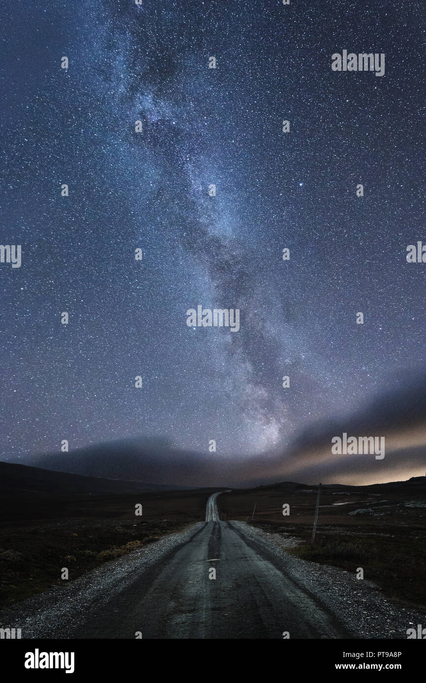 The road under starry sky with visible  Milky Way. Night in norwegian mountain area near Tydal, Stugudalen. Stock Photo
