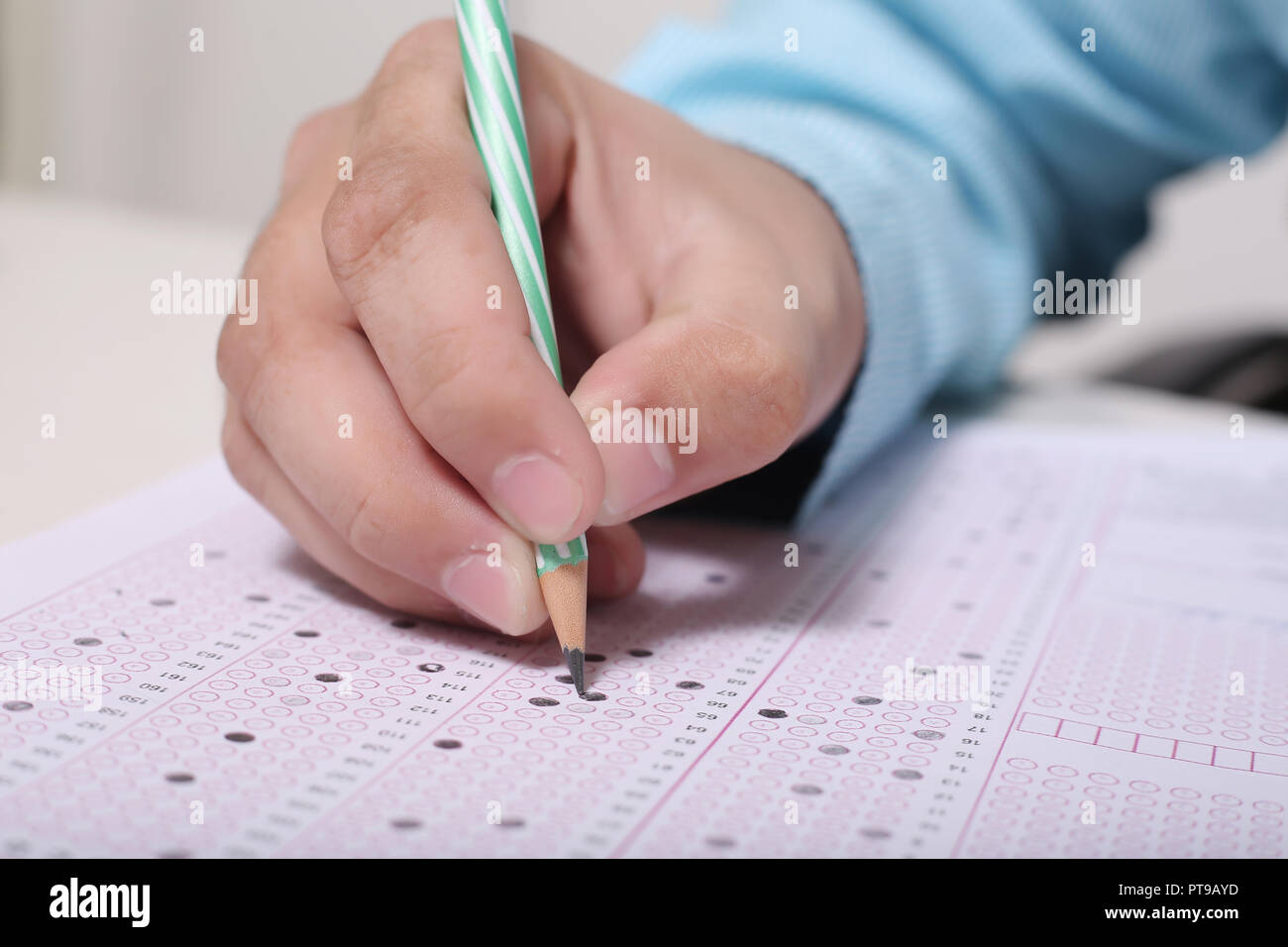 Man is filling OMR sheet with pencil. - Stock Image