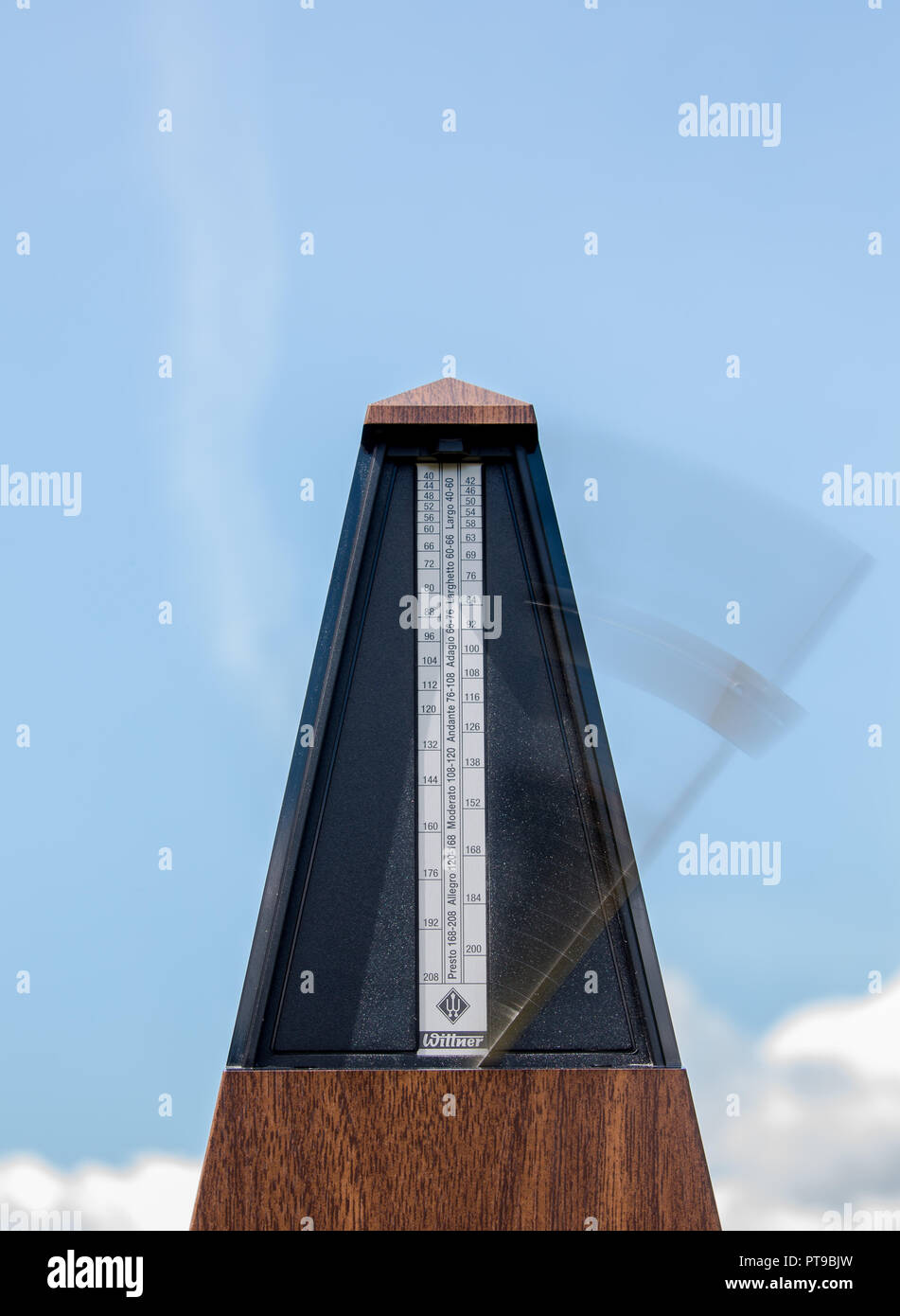 Portrait close up of musical timekeeping metronome in motion against blue sky background. Concept: time movement, time moving fast, time flies - Stock Image
