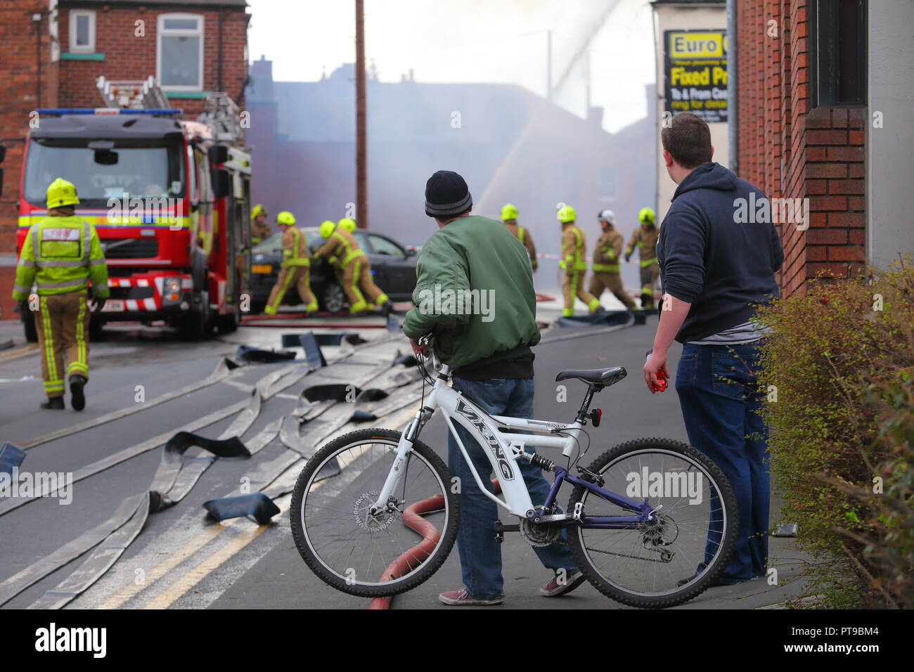 Onlookers at the scene of a fire incident in Castleford , West Yorkshire - Stock Image