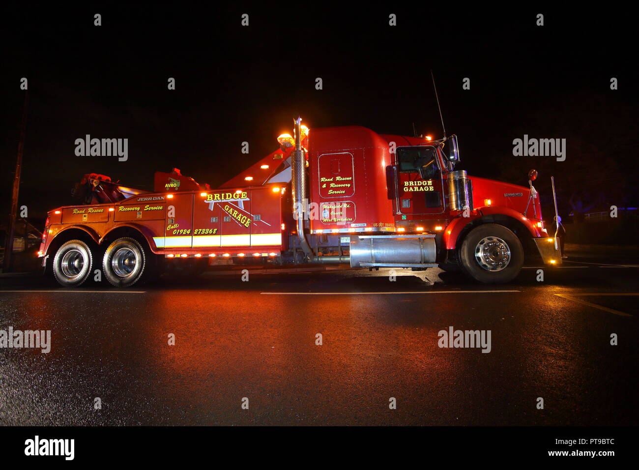 A Kenworth recovery truck arrives to the scene of an accident , where a double decker bus had hit a wall and leaving the bus leaning over. - Stock Image