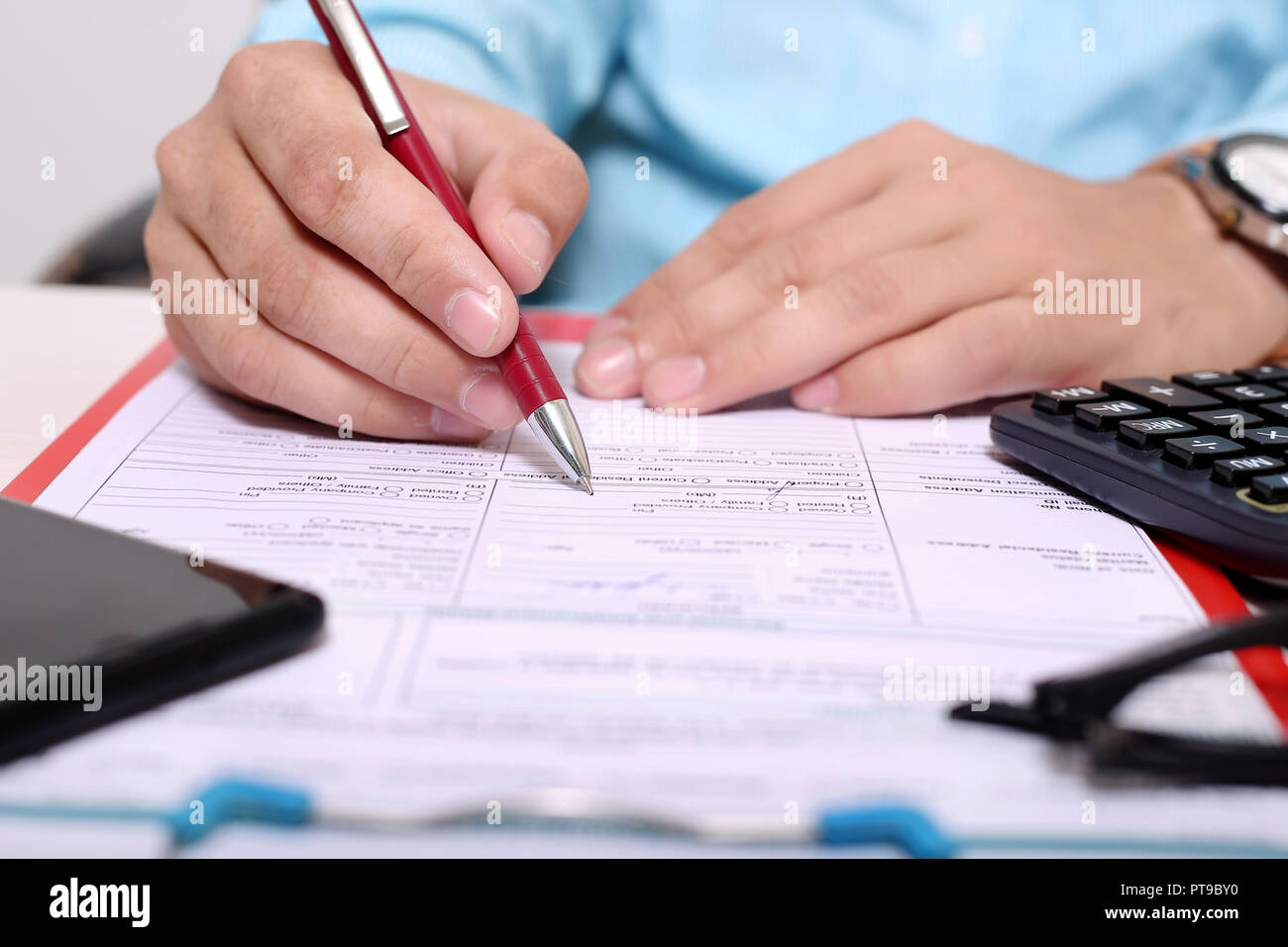 Man is filling form with pen. Picture of clipboard, form, glasses, calculator and phone. Stock Photo