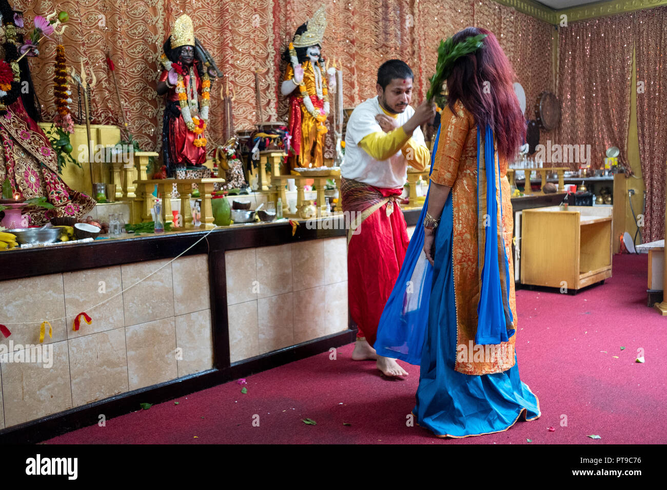 A woman in a beautiful sari gets a personal blessing & cleansing at a Hindu Mandir (temple) in Ozone Park, Queens, New York. - Stock Image