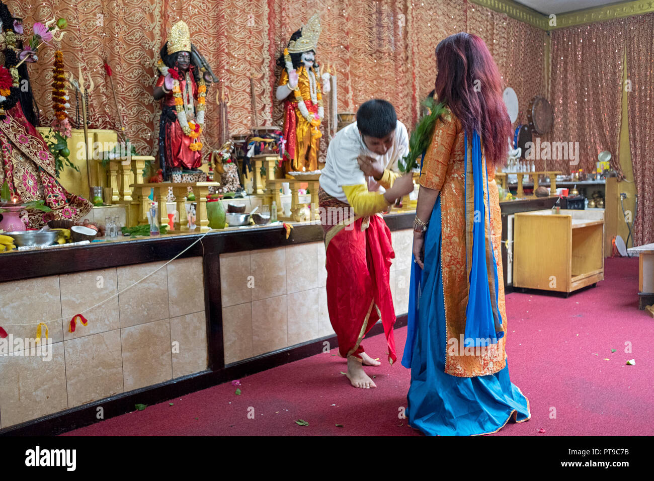A woman in a beautiful sari gets a personal blessing at a Hindu Mandir (temple) in Richmond Hill, Queens, New York. - Stock Image