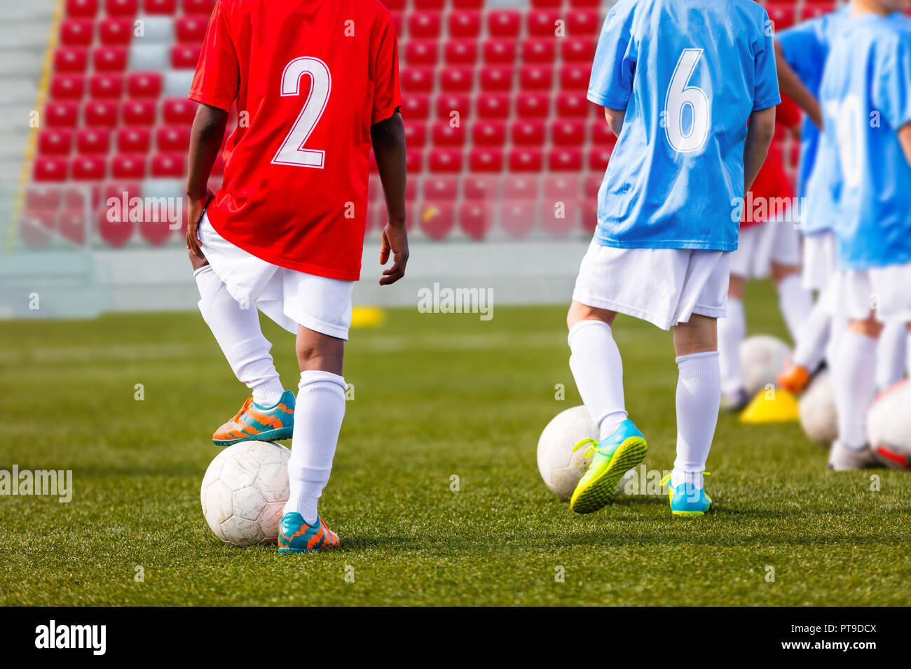 Boys soccer team training. Soccer football players training. Kids playing soccer on a stadium field. A multi-ethnic group of elementary age children p Stock Photo