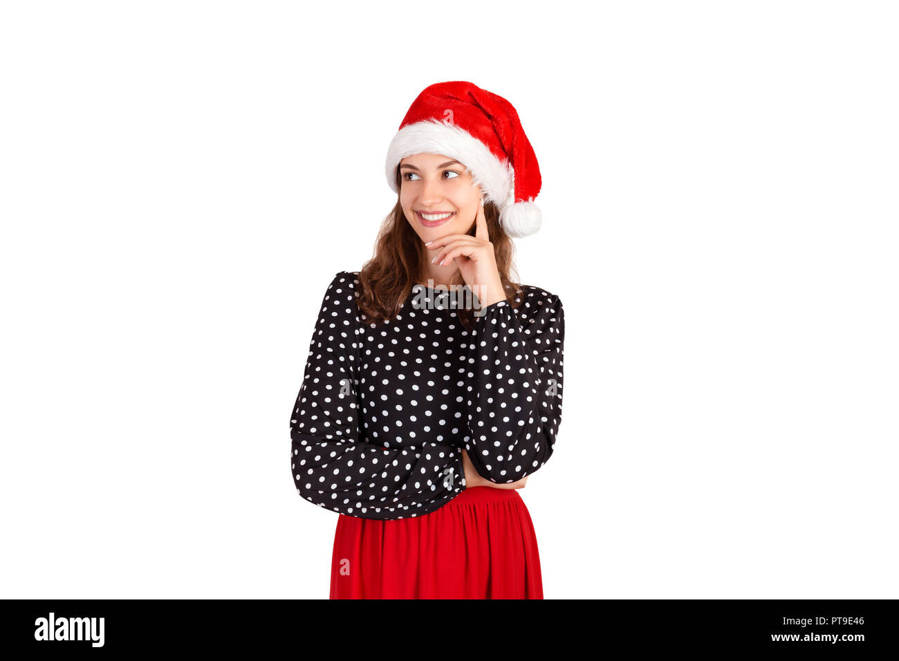 Confident attractive european woman standing with smiling broadly and glancing at left. emotional girl in santa claus christmas hat isolated on white  - Stock Image