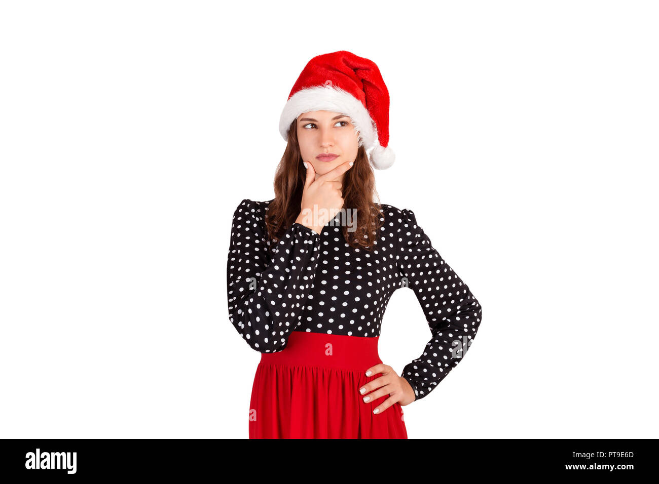 Dreamy attractive, thinking and confident young woman in dress, holding palm on cheek and gazing at upper left corner. emotional girl in santa claus c Stock Photo