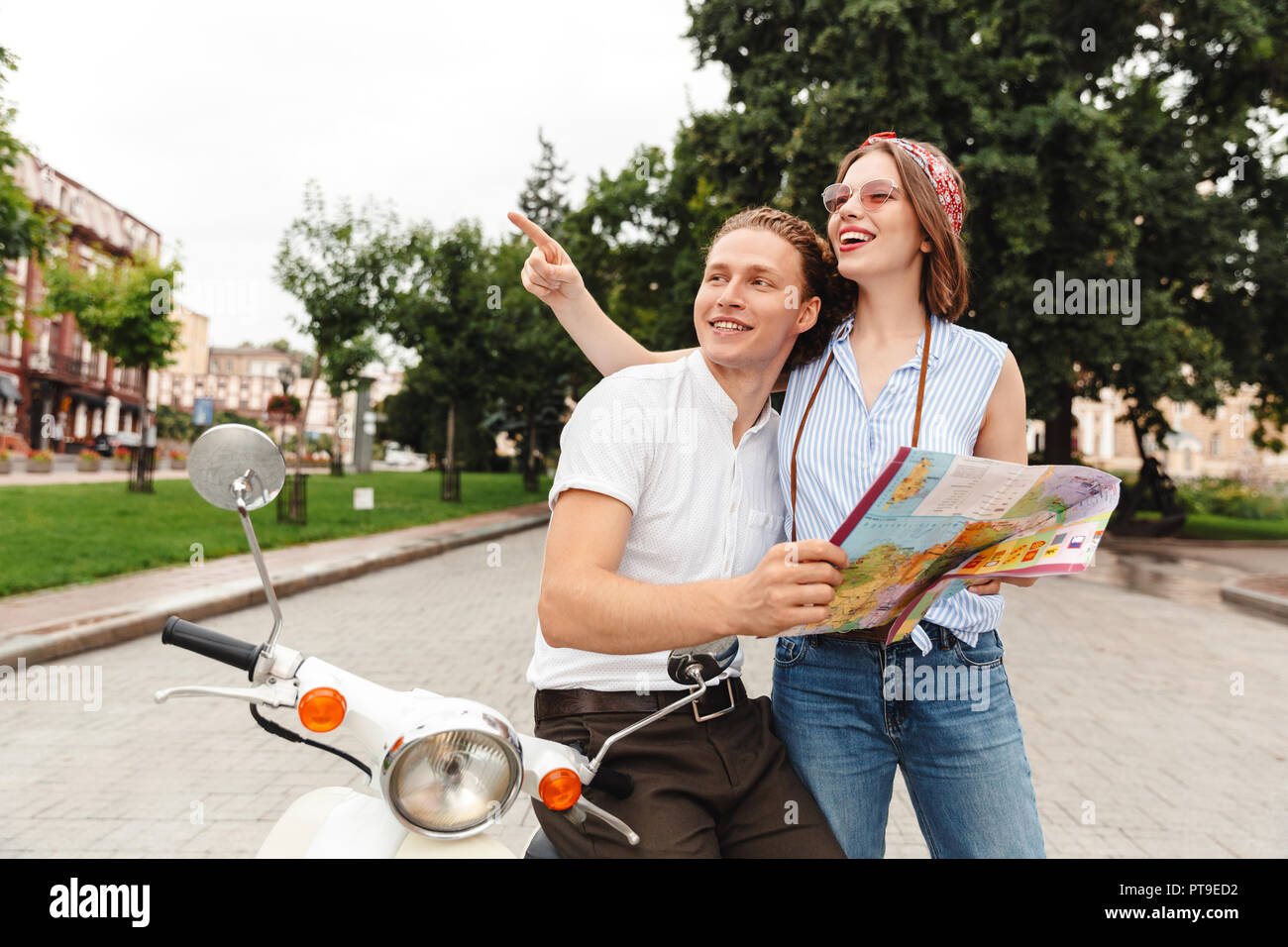 Happy Young Couple Standing Together With Motorbike At The