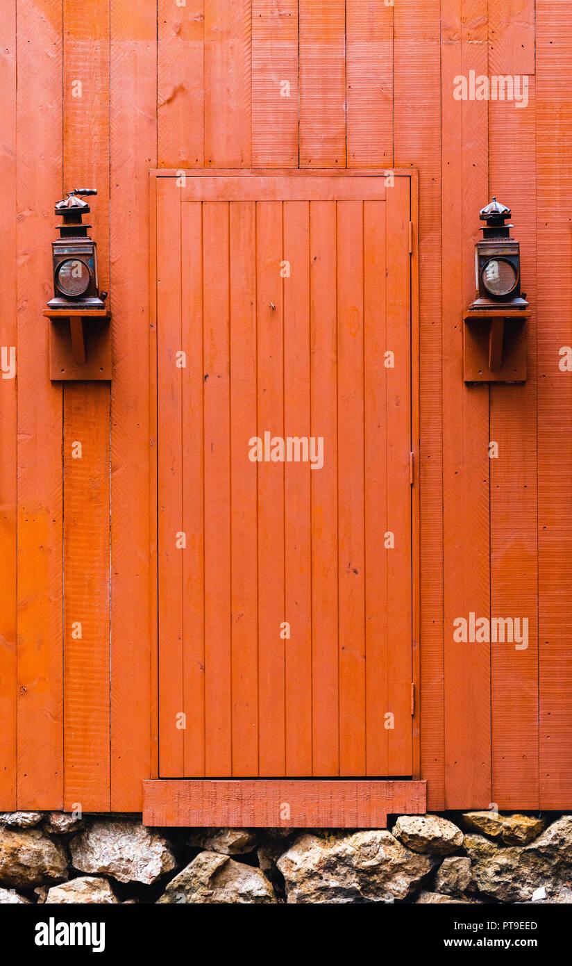 Old orange and red Western door between two old lanterns - Stock Image