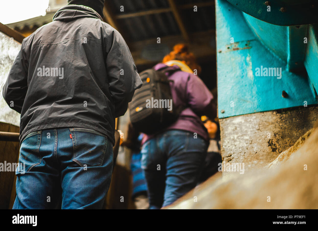 Dangerous looking man behind a woman with a bag in a purple jacket waiting in a queue - Stock Image