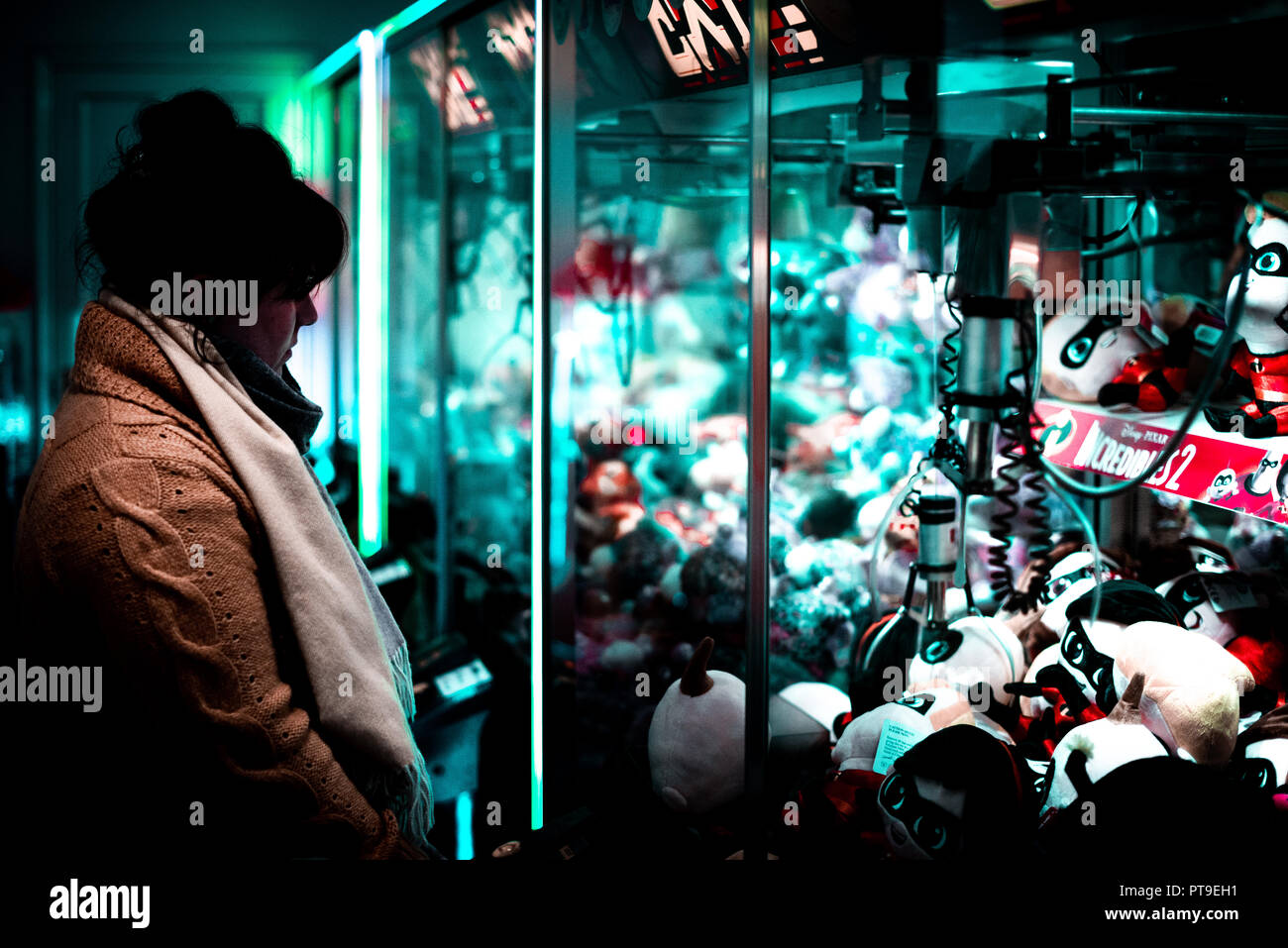 Depressive scene of a woman inside an amusements in the UK playing and losing on a claw machine against a blue light. - Stock Image