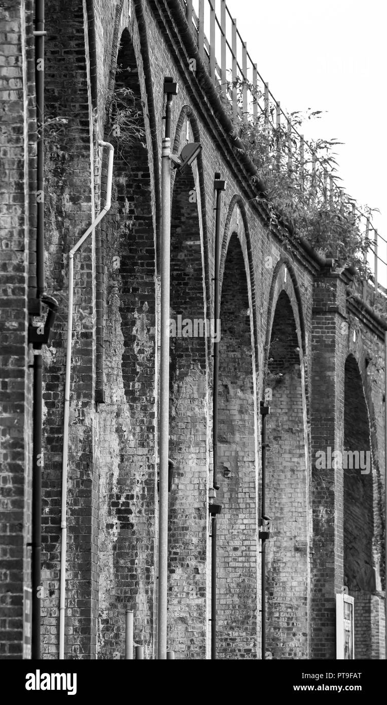Portrait, black & white, arty close up of tall bricked railway viaduct arches, Worcester City Centre. Worm's-eye view of outside architecture. - Stock Image