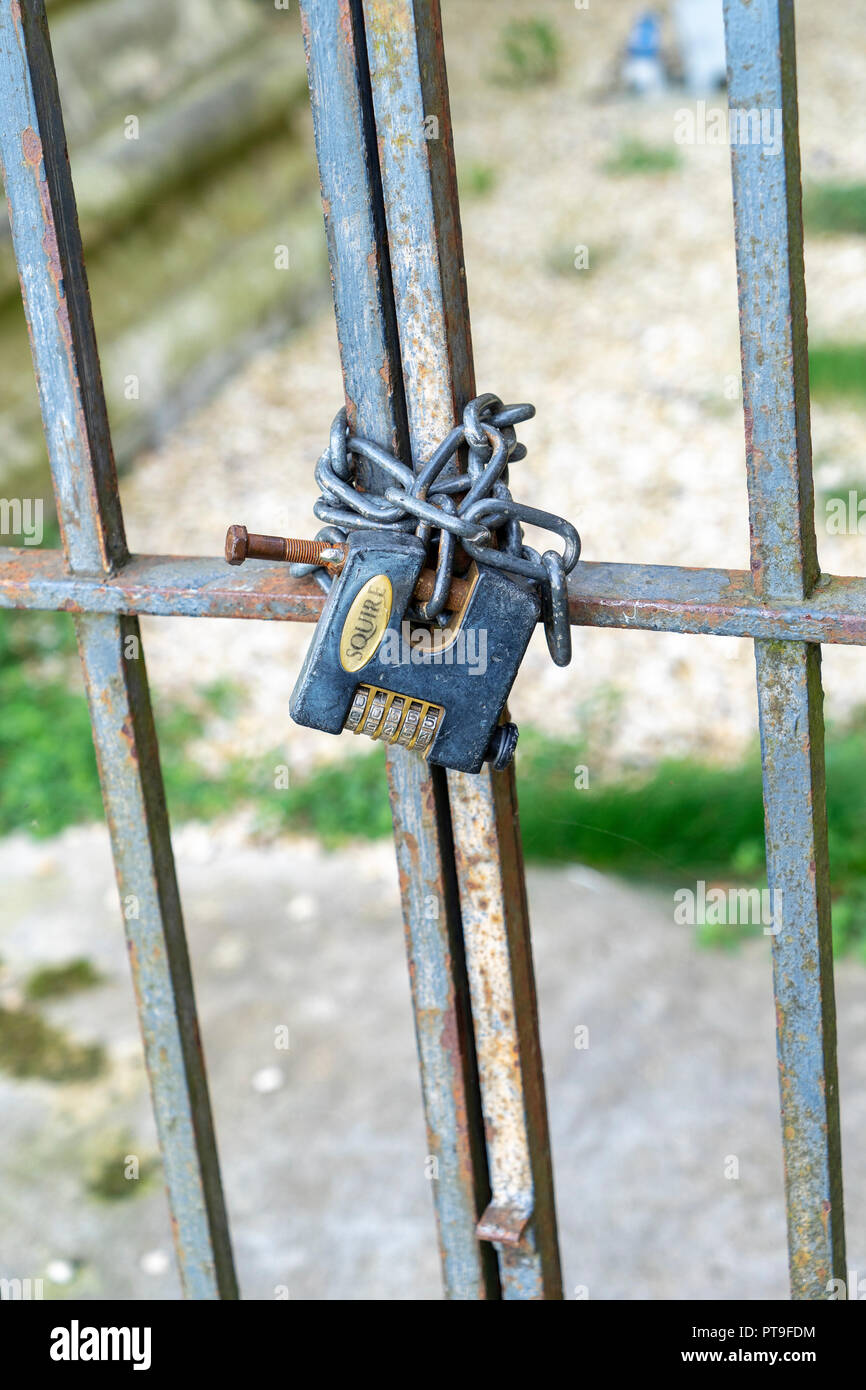 Heavy duty combination padlock with chain on gate - Stock Image