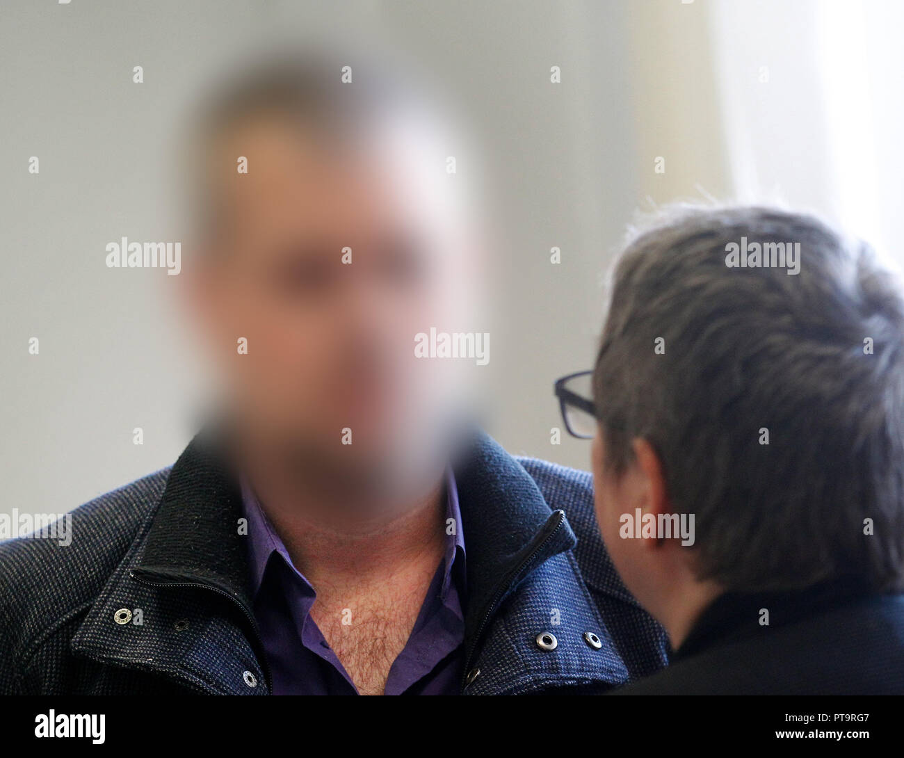 08 October 2018, North Rhine-Westphalia, Essen: A defendant accused of extortion is waiting for the trial to begin in Essen Regional Court and talks to his lawyer Gabriele Fengler-Trost before the trial begins. He is said to have threatened to poison food in a discount store between March and April 2018. The defendant had been arrested at the handover of 100,000 euros in cash. Photo: Roland Weihrauch/dpa - ACHTUNG: Person wurde aus rechtlichen Gründen gepixelt - Stock Image