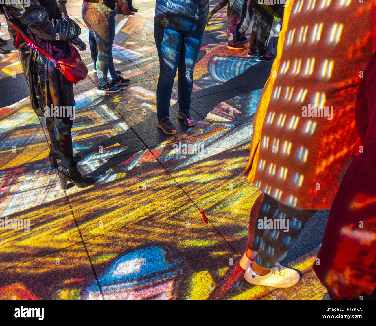 October 7, 2018 - Berlin, Berlin, Germany - People stand in the light of colorful projections as part of the 2018 Festival of Lights in Berlin, Germany October 7, 2018. Through several locations in the German capital including landmarks, museums and public buildings were lit with colorful artistic projections (Mapping) that work with the architecture of the building. (Credit Image: © Omer Messinger/ZUMA Wire) - Stock Image