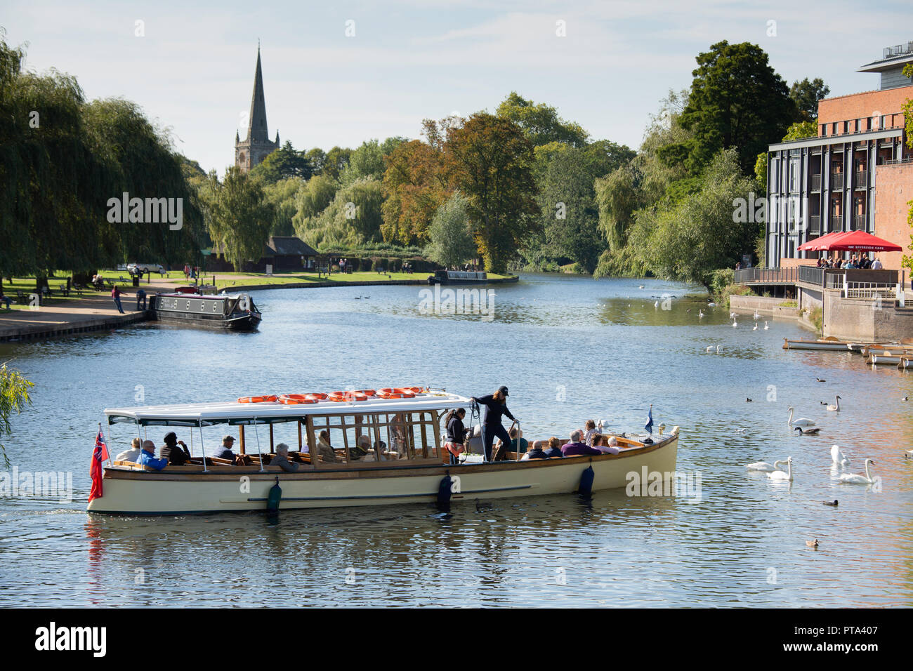 A river cruise ship taking tourists and visitors along the River Avon in Stratford upon Avon on a bright Autumnal day. - Stock Image