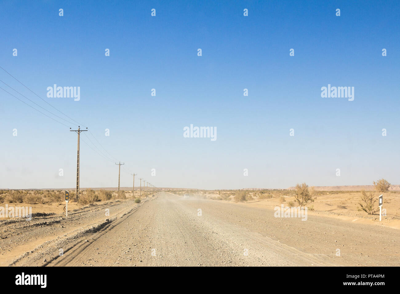 Dusty desert road in the Maranjab desert, in Iran, surrounded by sand and dry bushes, with the shape of a car visible in the background  Picture of a  - Stock Image