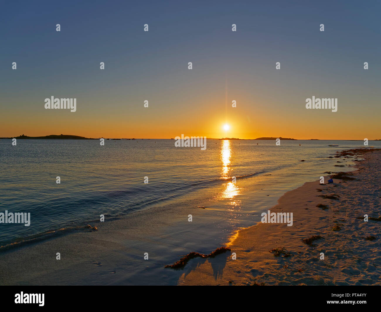 On a beach the setting sun reflects of the waters of the English Channel at Landeda, Brittany. Stock Photo