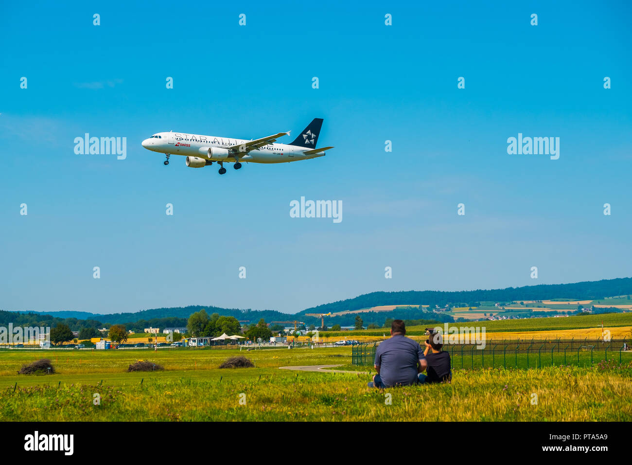 Father and son watching landing airplanes at Zurich airport at sunny day time - Stock Image