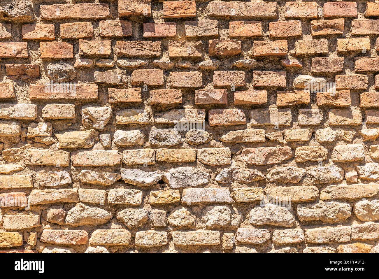Horizontal photo with texture. The texture shows the brick wall. Wall is old and worn. Wall is captured in San Gimignano in Italy Tuscany during the s - Stock Image