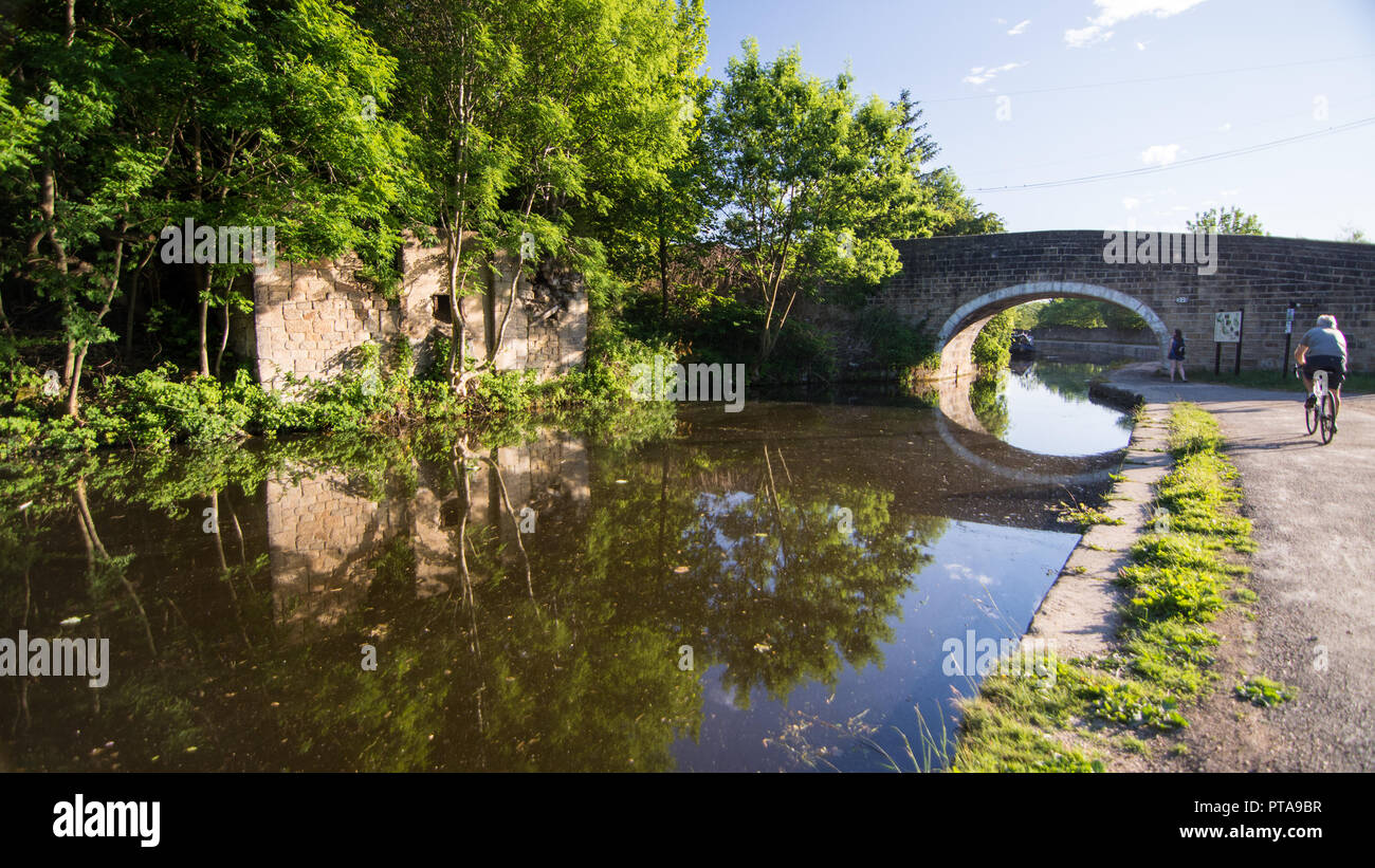 Leeds, England - June 30, 2015: A cyclist rides on the towpath alongside the Leeds and Liverpool Canal in West Yorkshire. - Stock Image