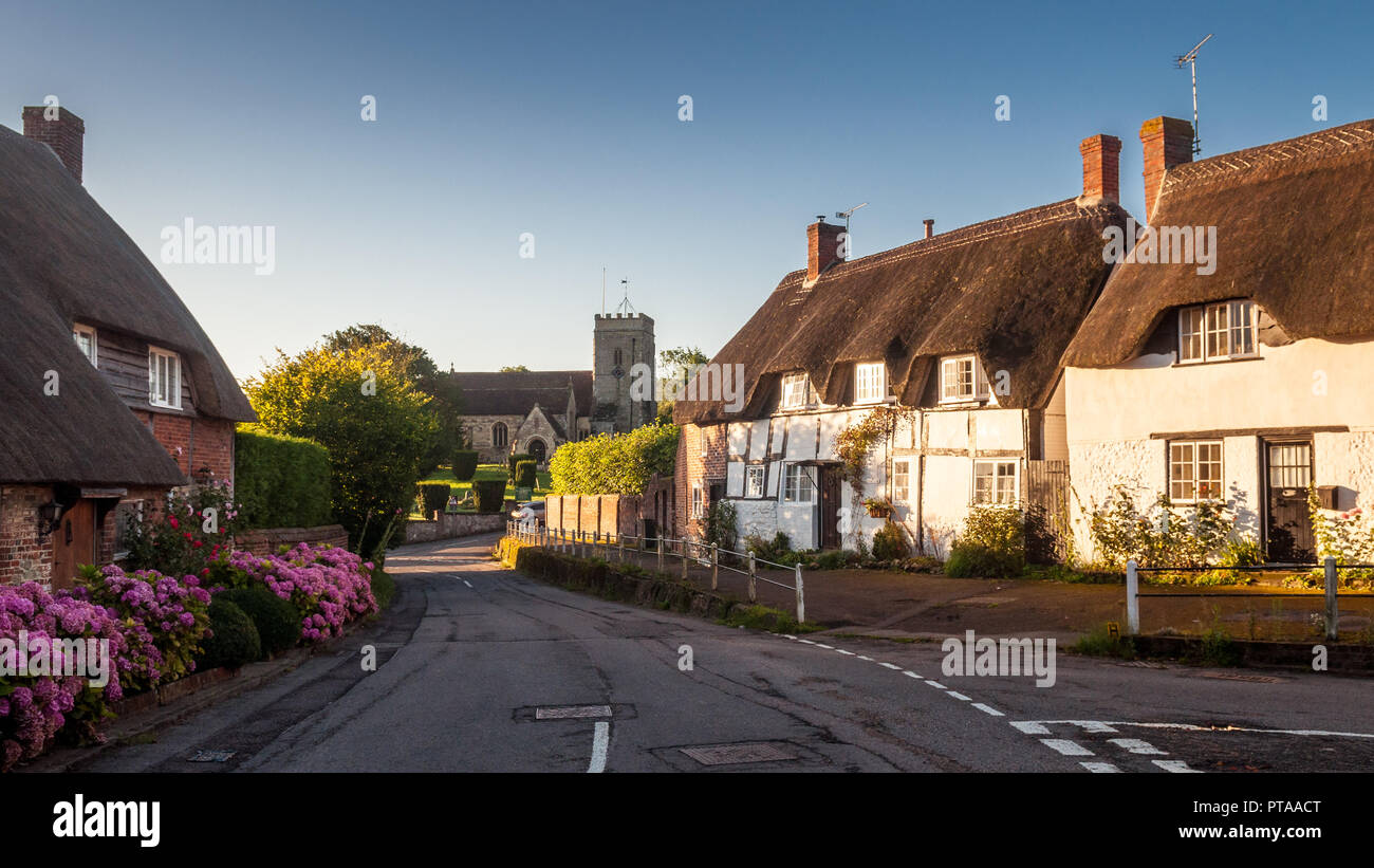Okeford Fitzpaine, England, UK - August 26, 2012: Traditional timbered and thatched cottages line a street in the village of Okeford Fitzpaine in the  - Stock Image