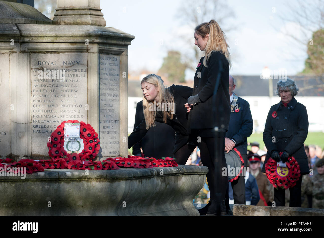 Chichester, West Sussex, UK. 12th November 2017. Two girls lay a poppy wreath at the cities war memorial during the Remembrance Sunday Service. - Stock Image