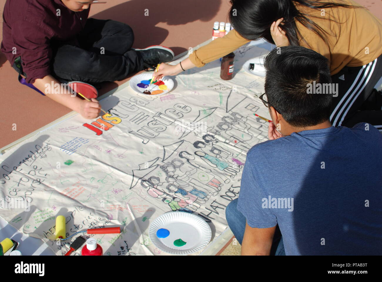 Activists with the Alameda Renters Coalition paint a banner before a City Council meeting at Alameda City Hall on April 4, 2017. - Stock Image