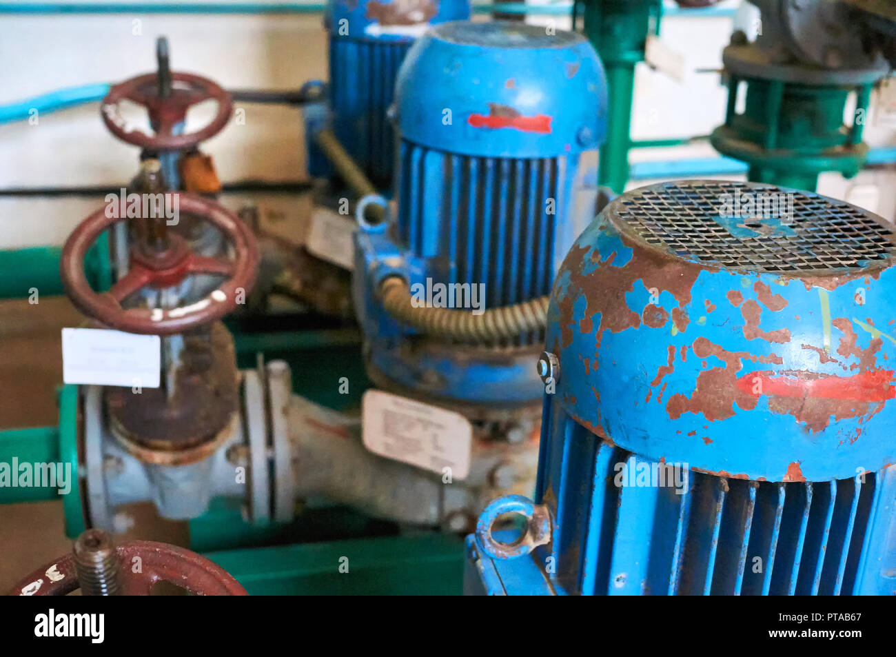 Old blue electric motor with pump, gate valve on the pipeline. Industrial background. - Stock Image