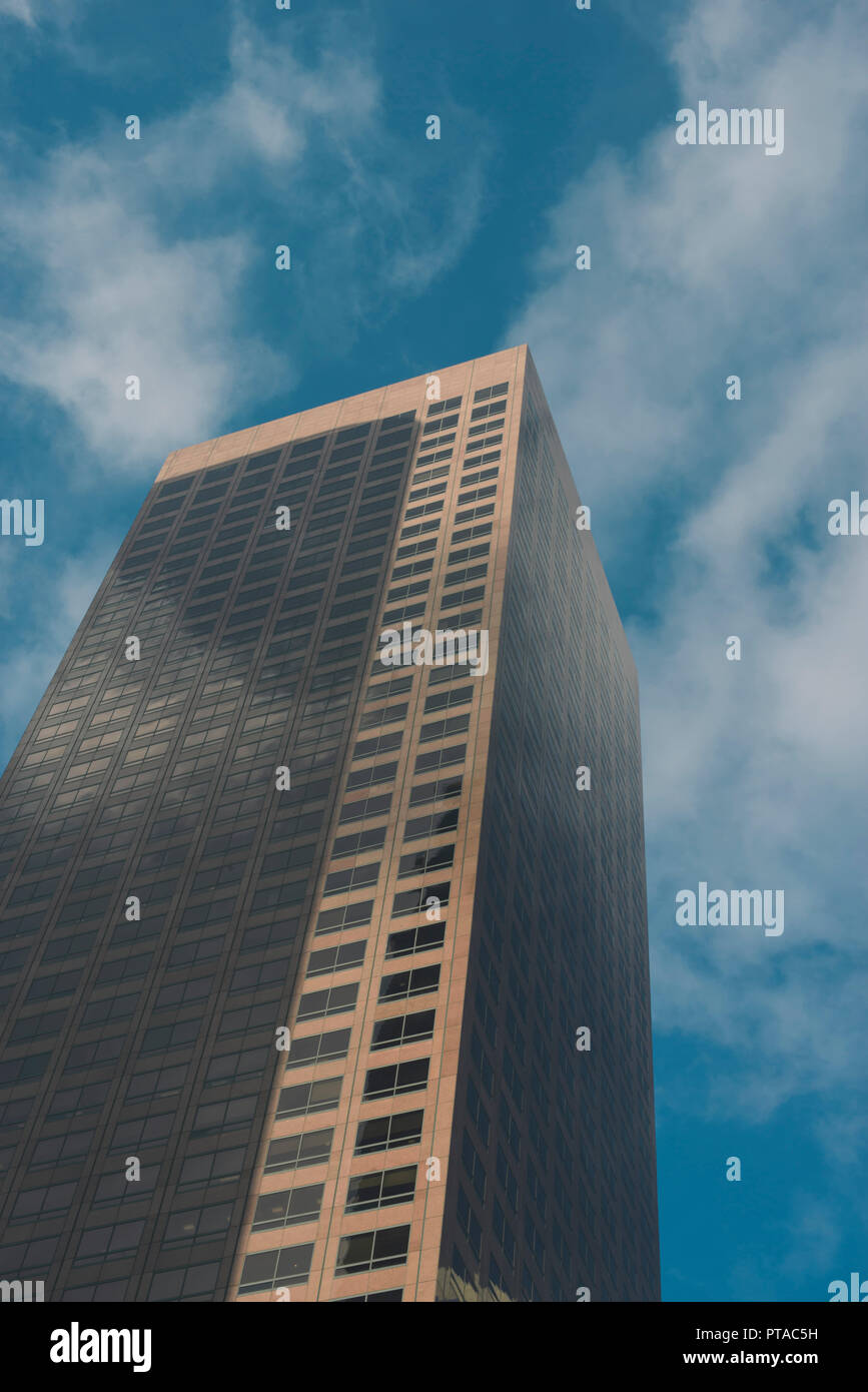 One tall city sky scraper with blue sky and clouds - Stock Image