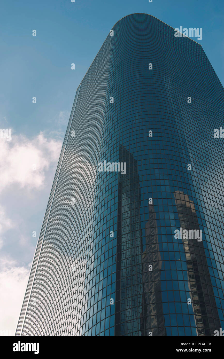 Tall sky scraper made of glass with sky and clouds - Stock Image
