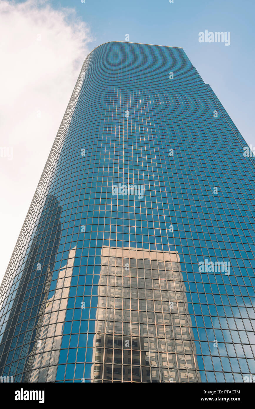 A tall glass sky scraper with reflections and blue sky - Stock Image