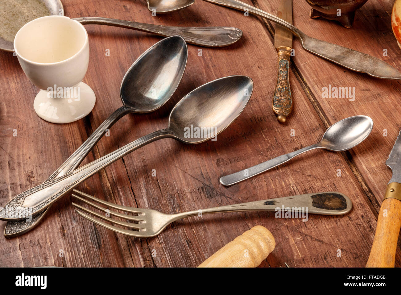 A photo of many vintage kitchen objects and cutlery from an old restaurant, flea market stuff on a wooden background Stock Photo