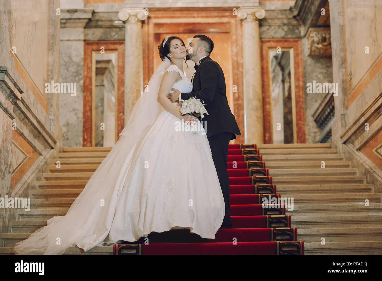 A beautiful young Turkish man wearing a black suit and a beard standing in  the home along with his beautiful bride in a white dress and a bouquet of f b389a9add