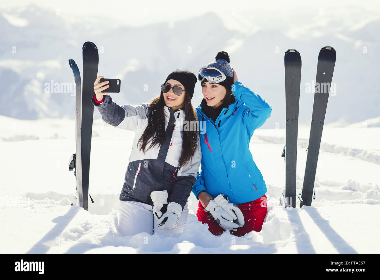 two young and active brunette sitting in the snowy mountains with ski and  make a selfie f6b5e3318